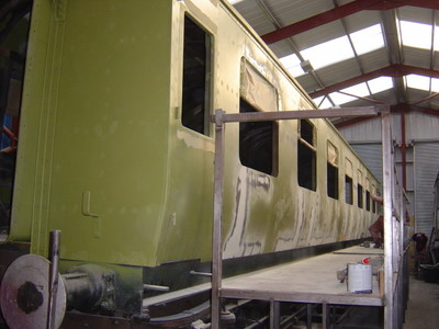 9th December: Bodywork repairs are complete, window apertures cut out and the refurbished brass window frames fitted. The doors have been hung and fitted. A first coat of metal primer has been sprayed on to highlight surface imperfections, and final body filling is under way.